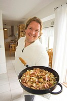 Man showing a pan of food