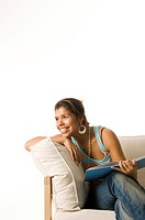 Woman looking away smiling while holding book