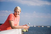 Woman with a bottle of drink smiling at the camera