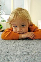Girl lying forward on the floor looking at the camera