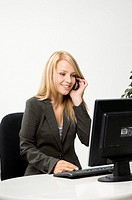 Businesswoman working while talking on the mobile (thumbnail)