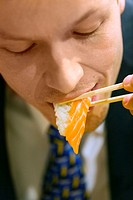 Businessman eating salmon sushi with chopsticks