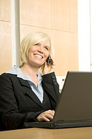 Businesswoman working on her laptop while talking on the mobile