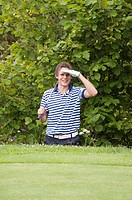 Man shielding his eyes while holding golf club (thumbnail)