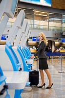 Businesswoman using an automated check-in machine (thumbnail)