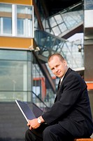 Businessman posing with laptop outdoors (thumbnail)