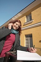Businesswoman writing while talking on the phone (thumbnail)