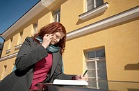 Businesswoman writing while talking on the mobile phone