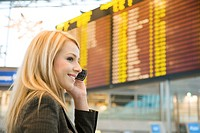 Woman talking on the mobile with arrival departure board in the background