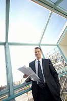 Businessman with paperwork smiling at the camera (thumbnail)