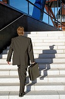 Businessman walking up the stairs of a building