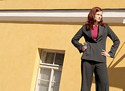 Businesswoman standing with arms akimbo holding mobile phone (thumbnail)