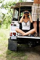 Couple at SUV Looking Through Binoculars