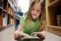 Pre-Teen Girl Reading in Library