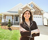 Hispanic woman in front of new house