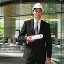 Mixed Race businessman holding blueprints