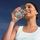 Mixed Race woman drinking glass of water