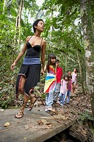 Hispanic woman and children exploring woods