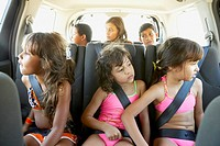 Hispanic children in car wearing seatbelts