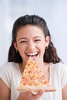 Hispanic girl eating pizza
