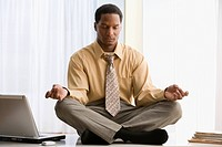 African American businessman meditating on desk