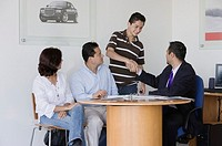 Hispanic family making deal with car salesman