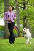 African American woman jogging with dog