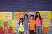 Multi-ethnic children in front of mural