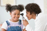 African American female doctor examining girl's ear