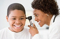 African American female doctor examining boy&#8217;s ear