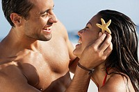 South American man holding starfish in girlfriend´s hair