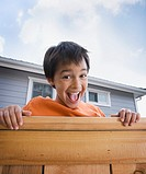 Hispanic boy laughing over fence