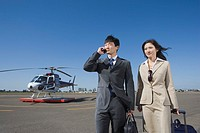 Asian businesspeople waking away from helicopter