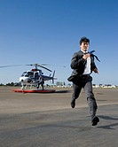 Asian businessman running away from helicopter