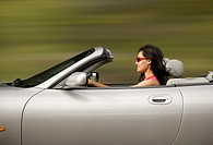 Hispanic woman driving convertible car