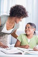 African American mother helping daughter with homework