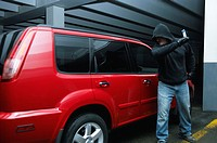 Vandal breaking into a minivan