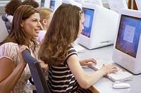 Teacher helping schoolgirl at computer