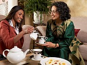 Indian mother and adult daughter having tea