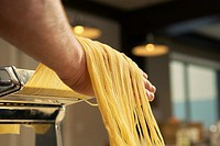 Cook taking spaghetti from pasta machine (thumbnail)