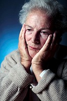 Depressed elderly woman resting her head in her hands