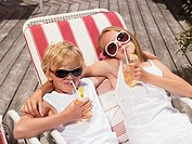 Brother and sister lying in deck chairs, drinking juice