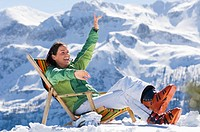 Woman in mountains sitting in deck chair
