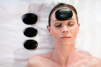 Woman relaxing a hot stone on her forehead