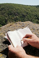 Man writing notes in notebook