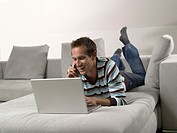 Man lying on sofa, using laptop and mobile phone