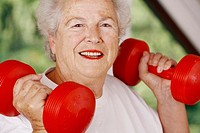 Elderly woman exercising her arm muscles by lifting dumbbells