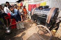 Water collection  Men collecting clean water from a mobile water dispenser  Photographed at a slum in Dhaka, Bangladesh, in 2006