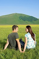 Young couple sitting in mountain field back view