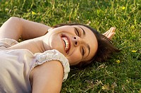 Smiling young woman lying on grass close up